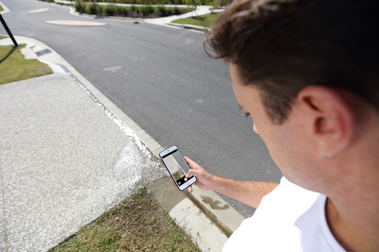 Man taking a photo on mobile phone to report a water leak on street