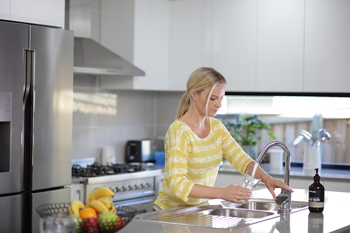 Woman getting a glass of from kitchen tap