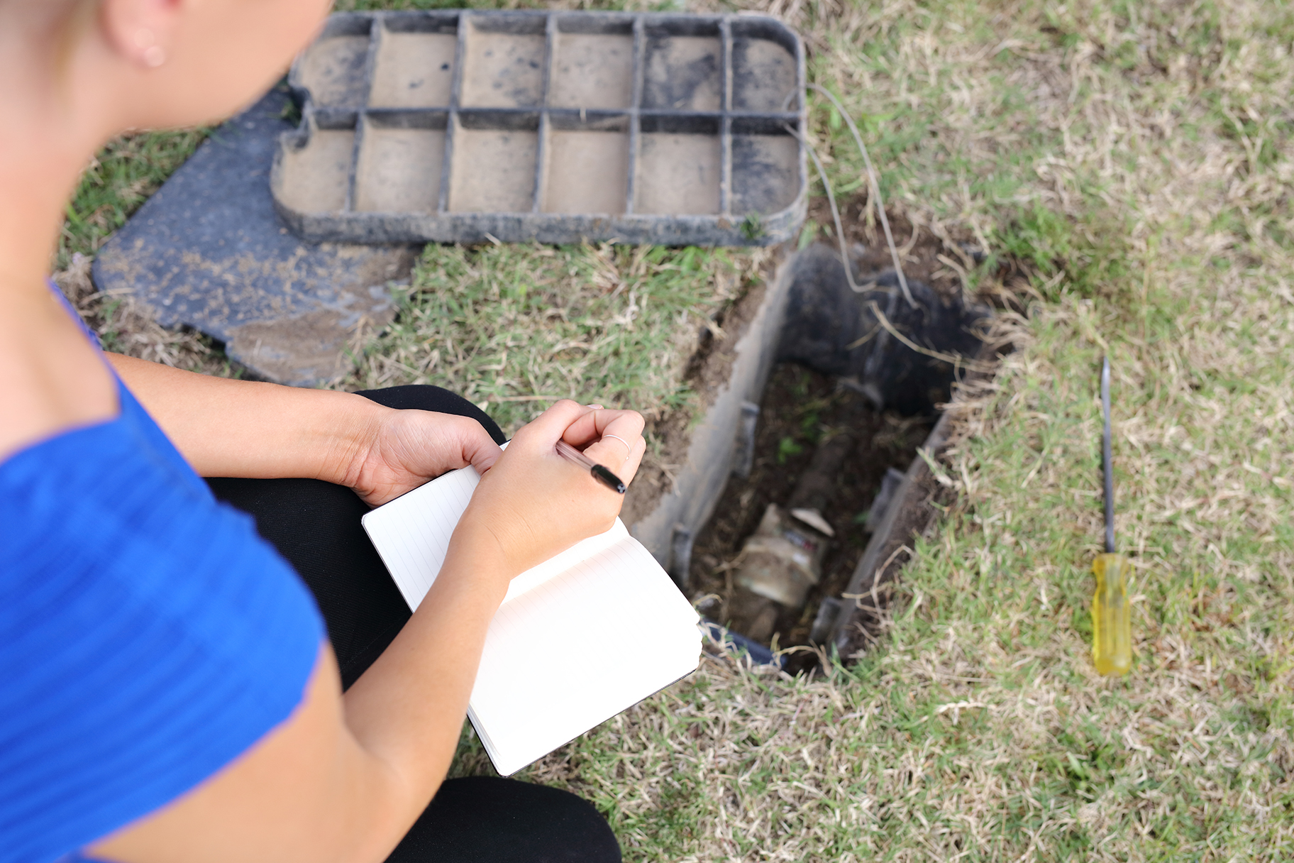 Woman recording water meter reading