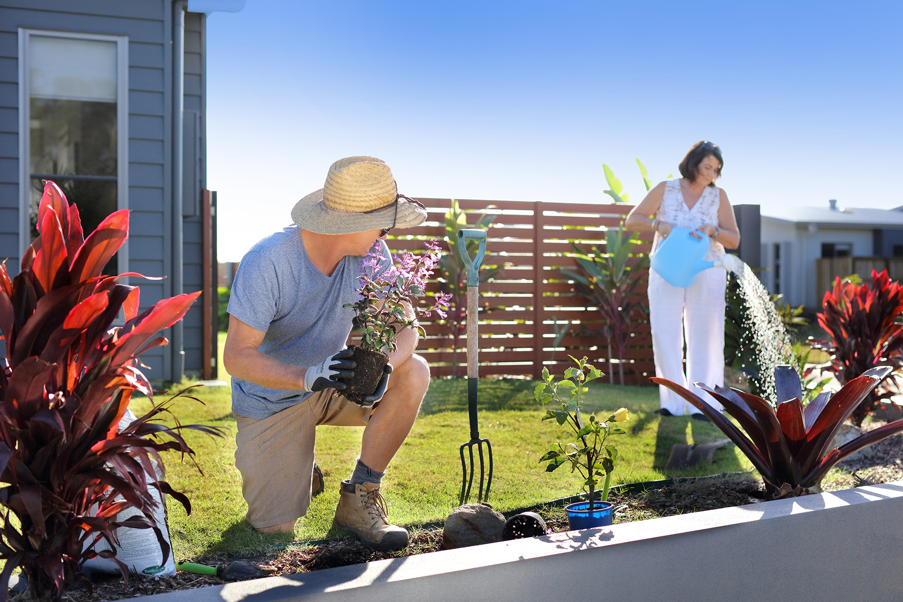 Man planting flowers and woman watering garden in residential garden