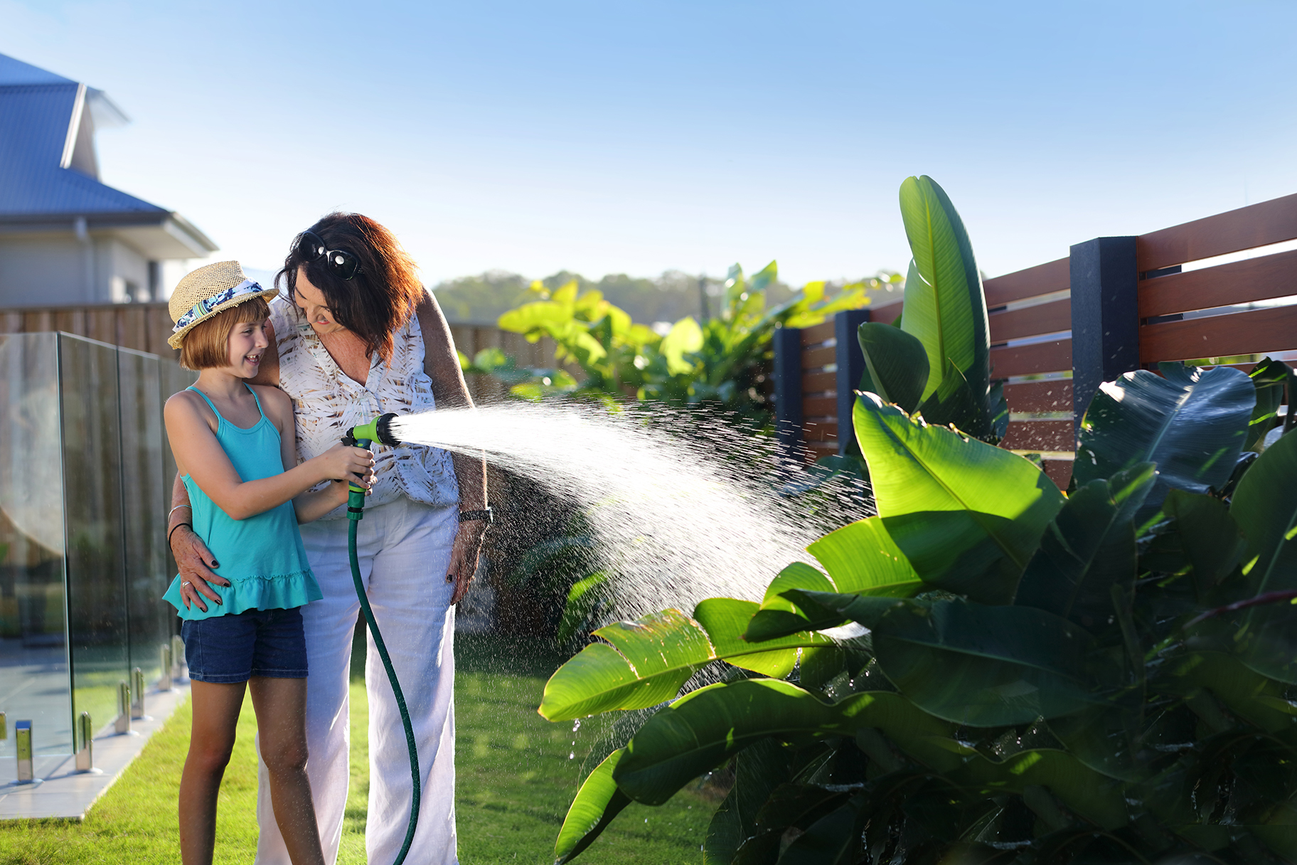 Woman and girl watering residential garden with hose