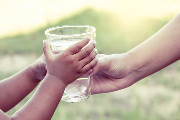 Woman handing child a glass of water