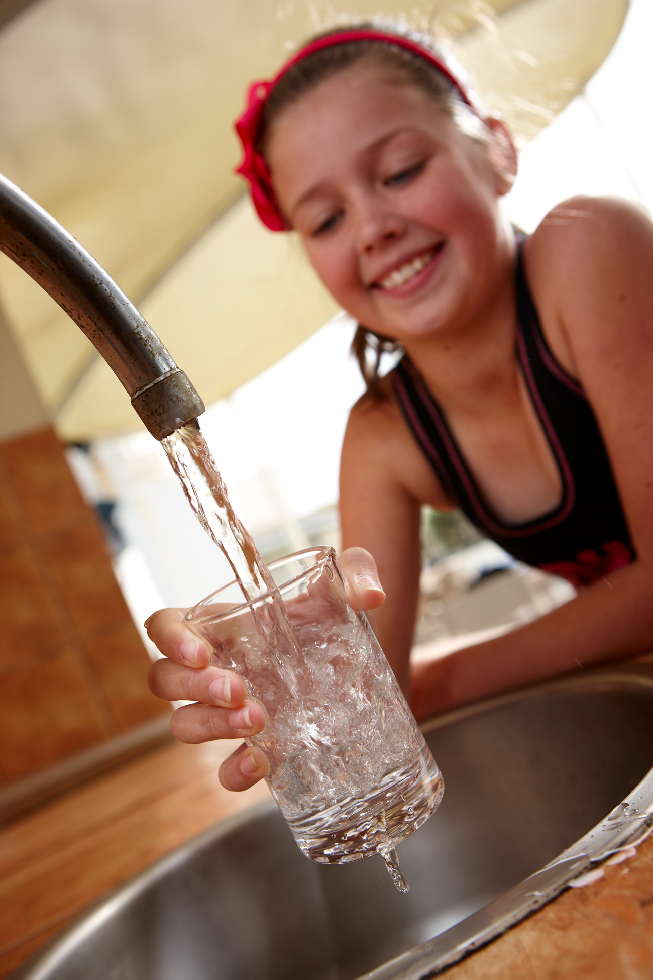 Girl filling glass of water from tap