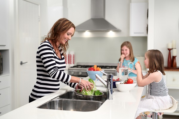 Mother and daughters at kitchen sink