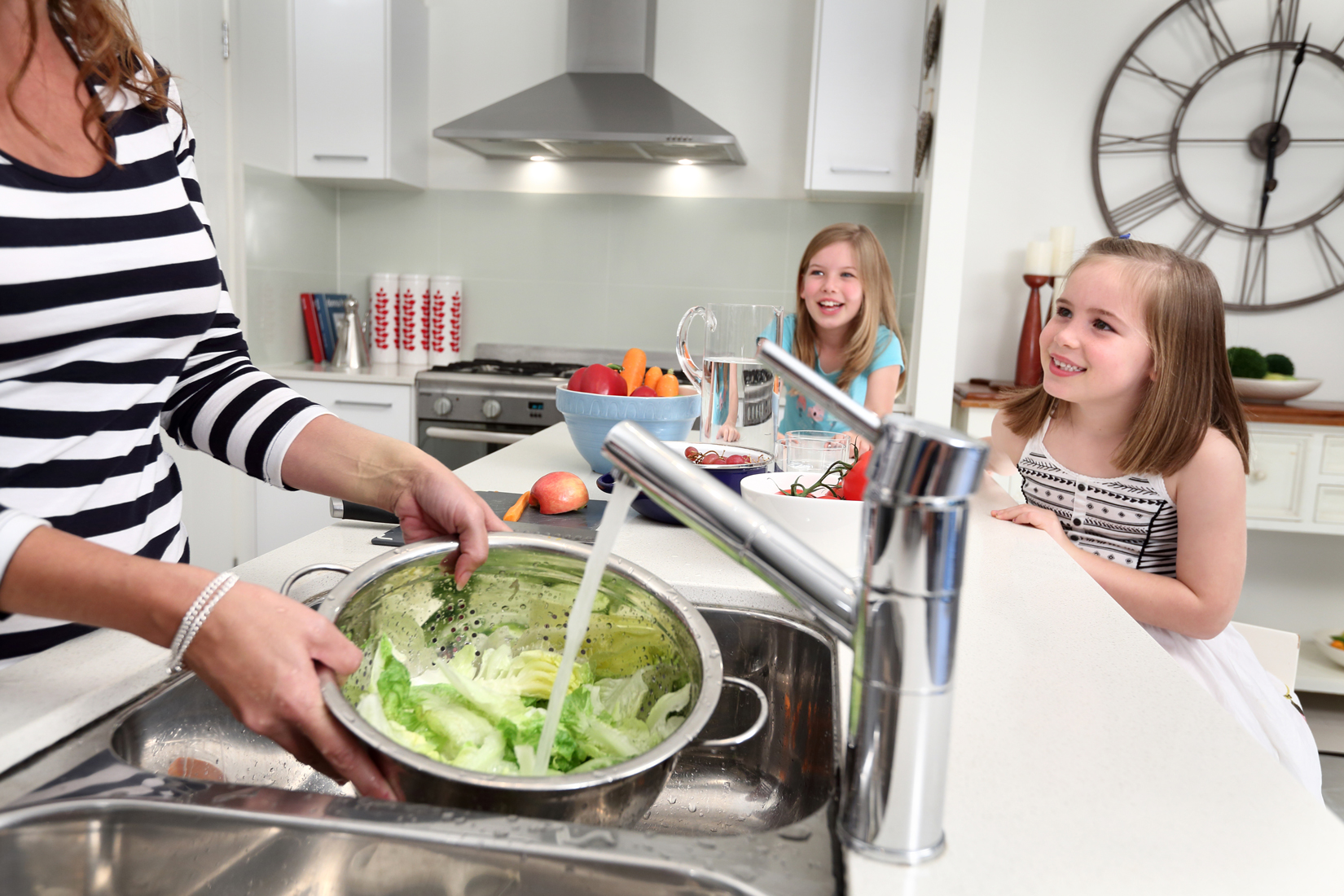 Mother washing lettuce at kitchen sink