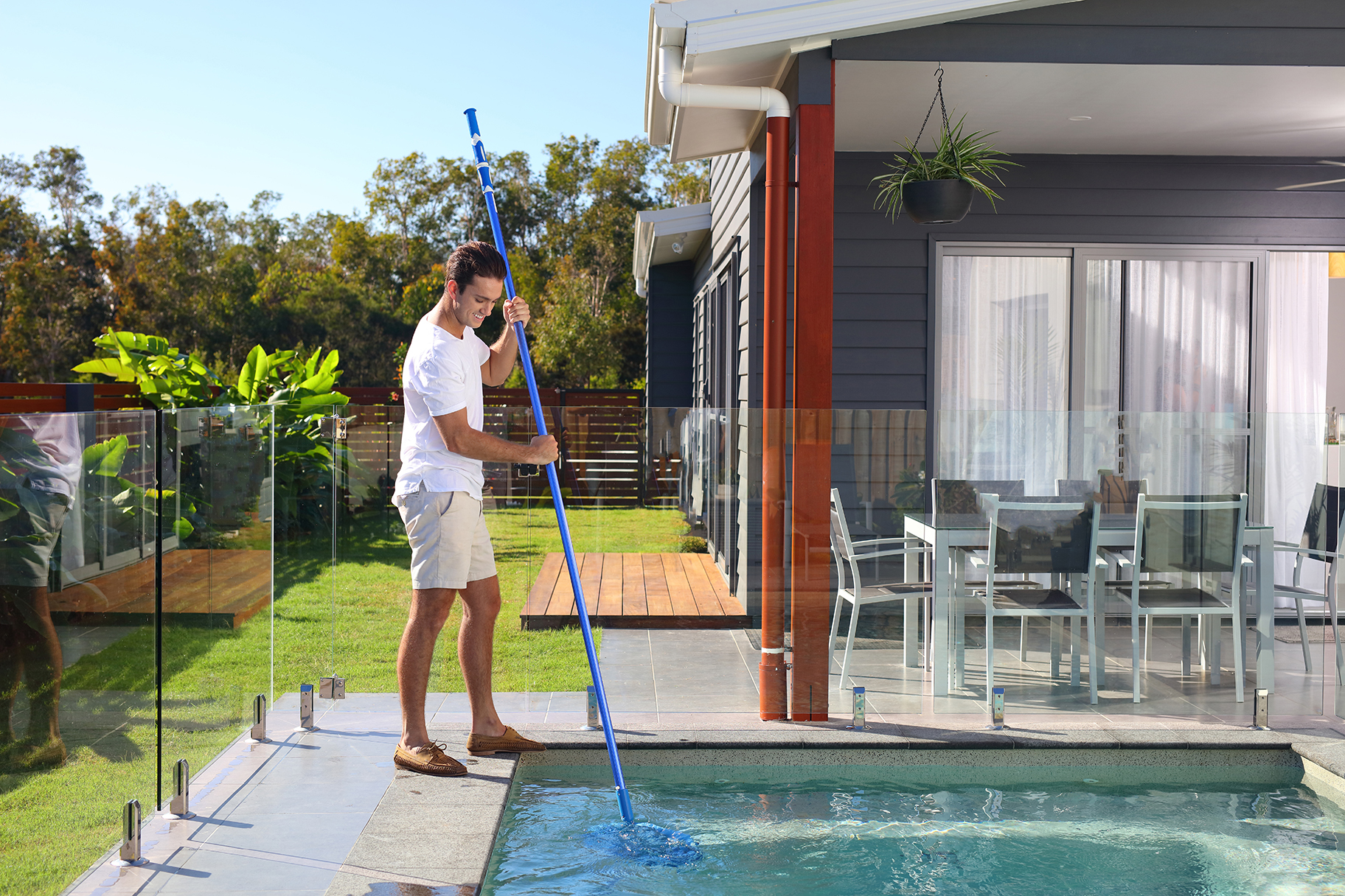 Man cleaning pool in residential backyard