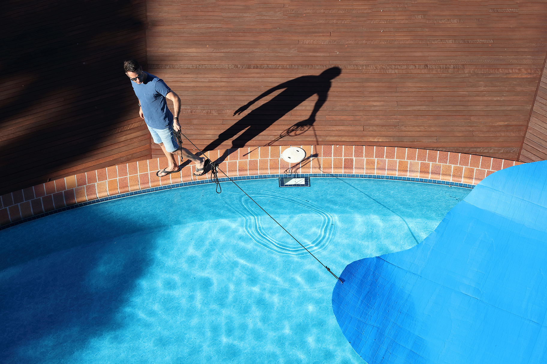 Man covering residential pool with blue tarp