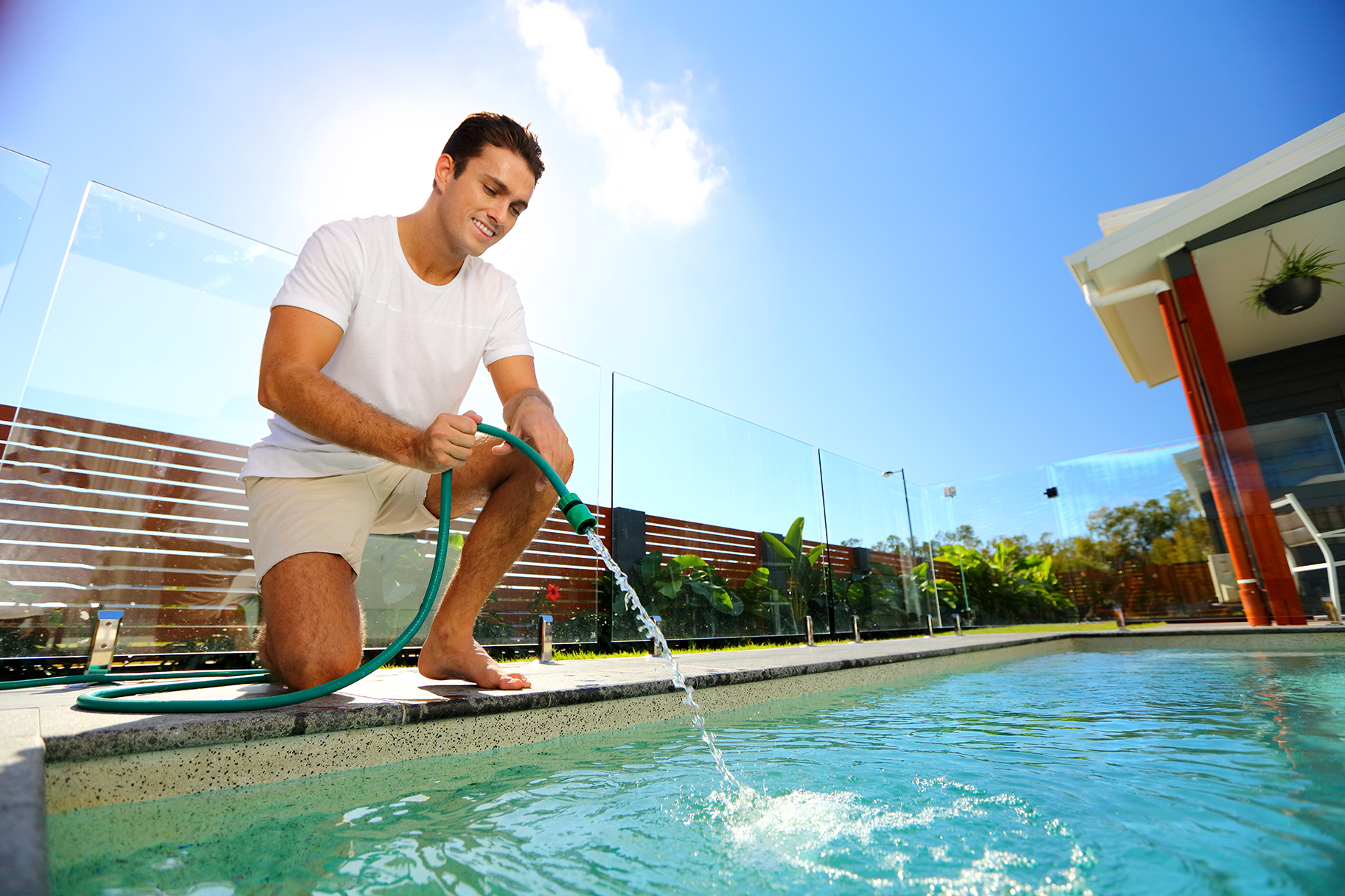 Man filling residential pool water up with hose