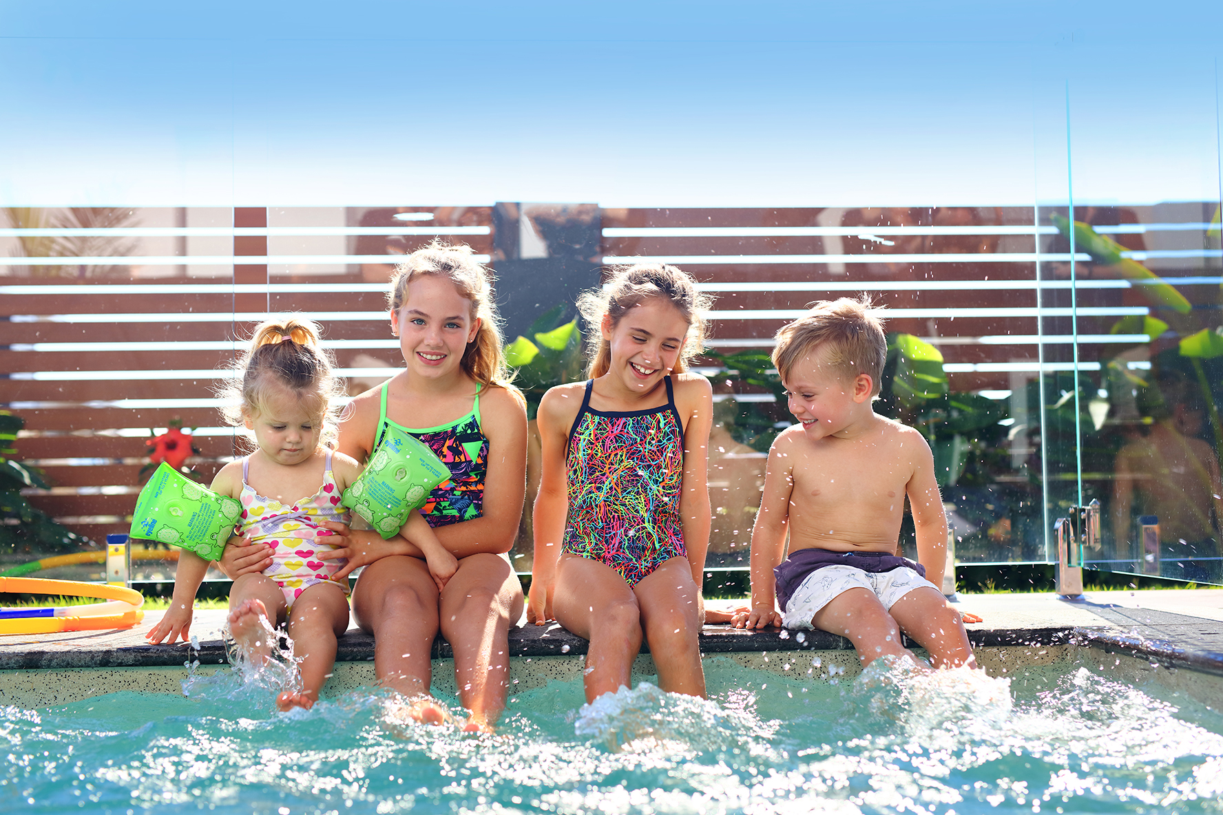 Kids sitting by residential pool